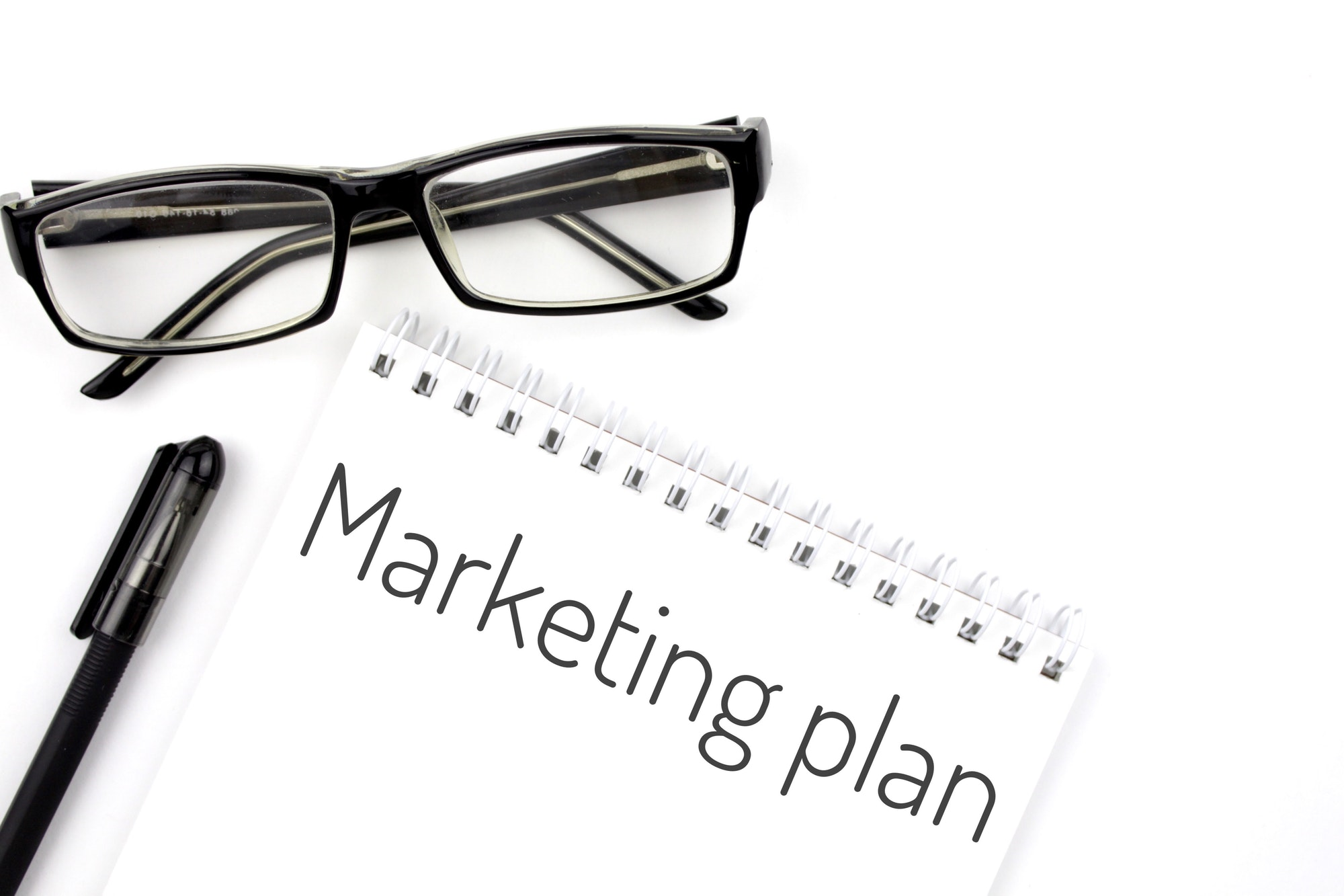 Reading glasses and notebook with word marketing plan on a white background