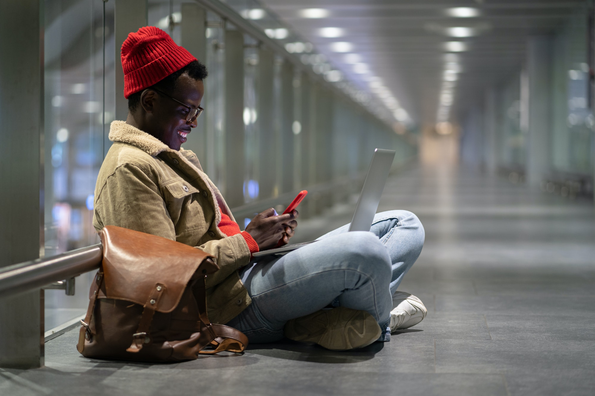 Stylish Black millennial man sitting in empty hall of airport, using phone, chatting in social media